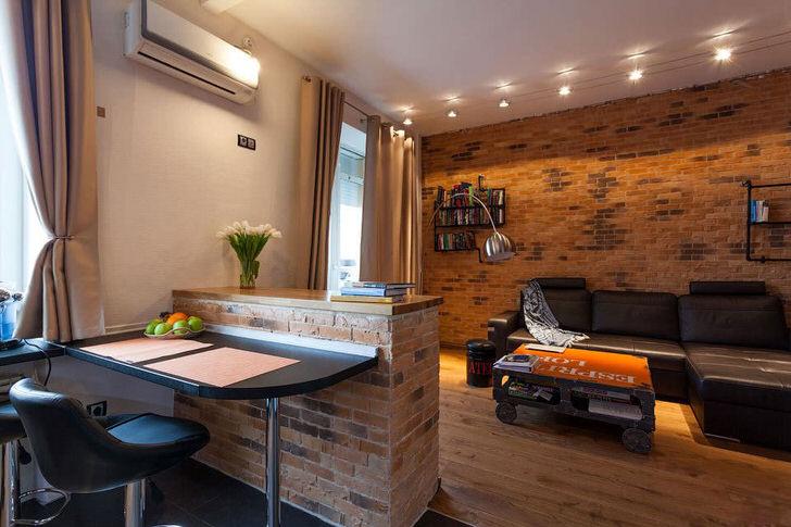 Стена в гостиной декорирована в соответствии со стилем лофт. Кирпичная кладка является одним из наиболее популярных элементов.
