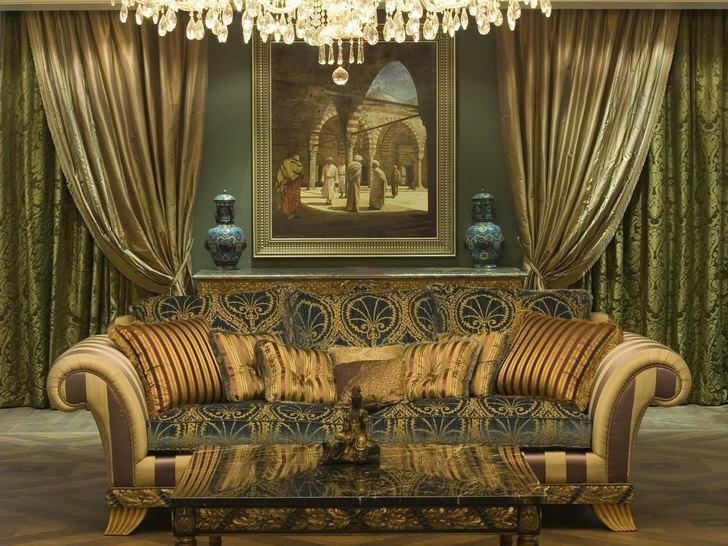 Стильный массивный диван с мягкой обивкой украшен подушками разных размеров в соответствии со стилем барокко .