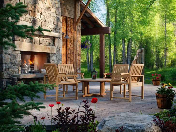 Зона отдыха примечательна большим камином, который не только визуально украшает двор, но и делает атмосферу уютной и романтической.