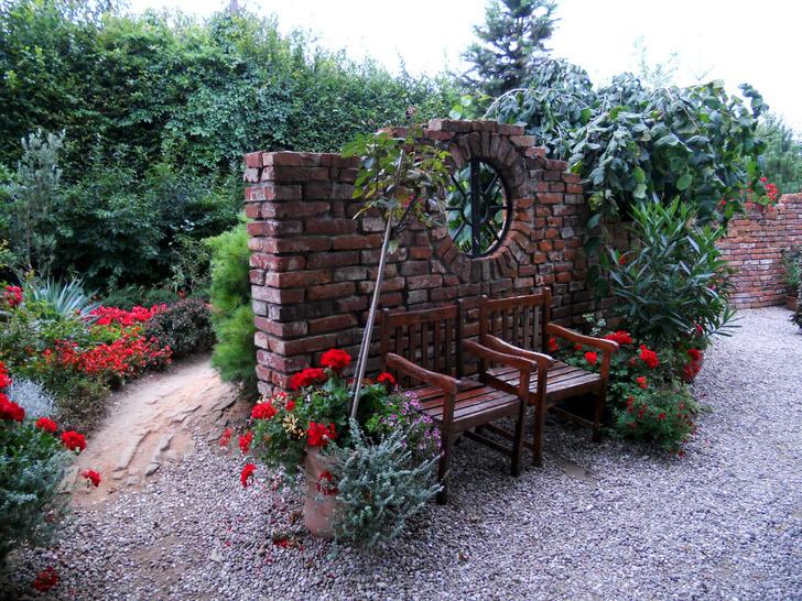 Романтические мотивы в саду, оформленном в стиле модерн. Стена из темного кирпича и красные цветы притягиваются взгляд и завораживают.