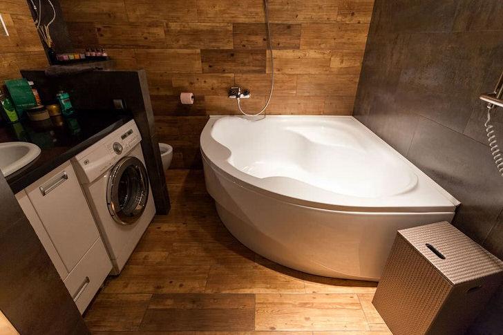 Угловая ванна позволяет сэкономить пространство. Интерьер в стиле лофт примечателен использованием отделочных материалов из дерева.