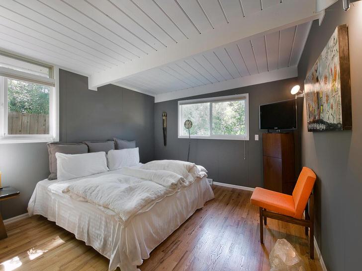В центре композиции находится пышная кровать с мягкими, объемными подушками и одеялами, такими как в доме у бабушки в деревне