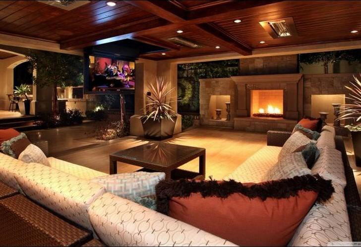 Стильная комната для гостей в современном деревенском стиле украшена большим камином. деревянные потолки органично вписываются в общий интерьер.