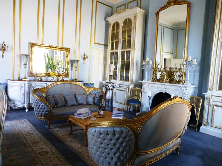 Гостиная в ампир стиле выполнена в нежно-голубых тонах, которые гармонично сочетаются с золотыми элементами декора. Обрамление зеркал и резные элементы мебели выполнены в едином стиле.