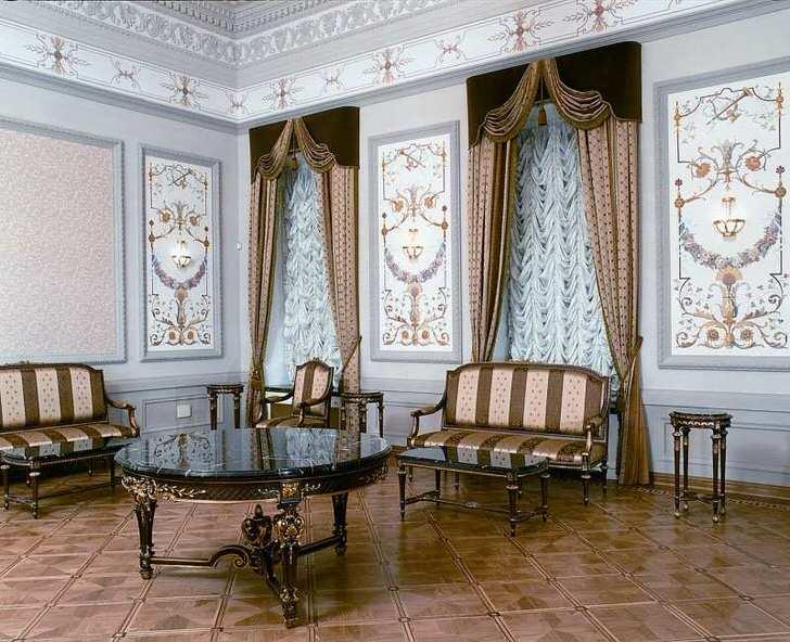 Окна в гостиной завешены плотной, драпированной занавеской и украшены темными ламбрекенами.