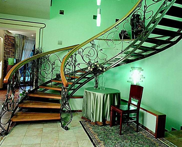 Классика стиля в сочетании материалов и плавности линий изящной лестницы.
