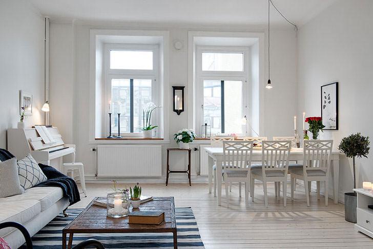Стильная гостиная разделена на зону отдыха и обеденную зону. В соответствии со скандинавским стилем стены комнаты оформлены в белом цвете.