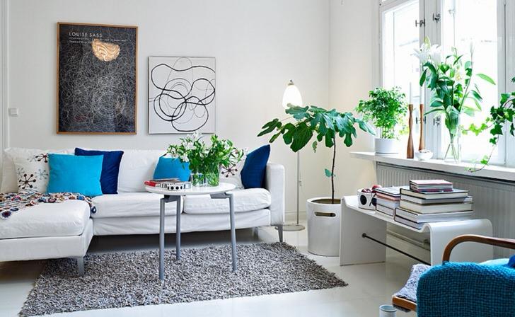Сочные акценты синего и бирюзового органично смотрятся на фоне белой отделки стен гостиной. В соответствии со стилем в оформлении комнаты использованы цветы.