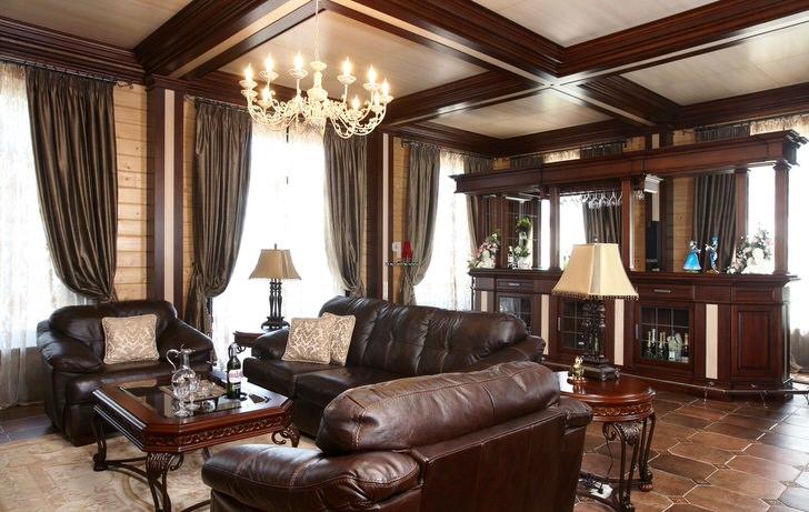 Шикарная комната для гостей с барной стойкой. Внимание притягивает массивная мягкая мебель, оббитая кожей.
