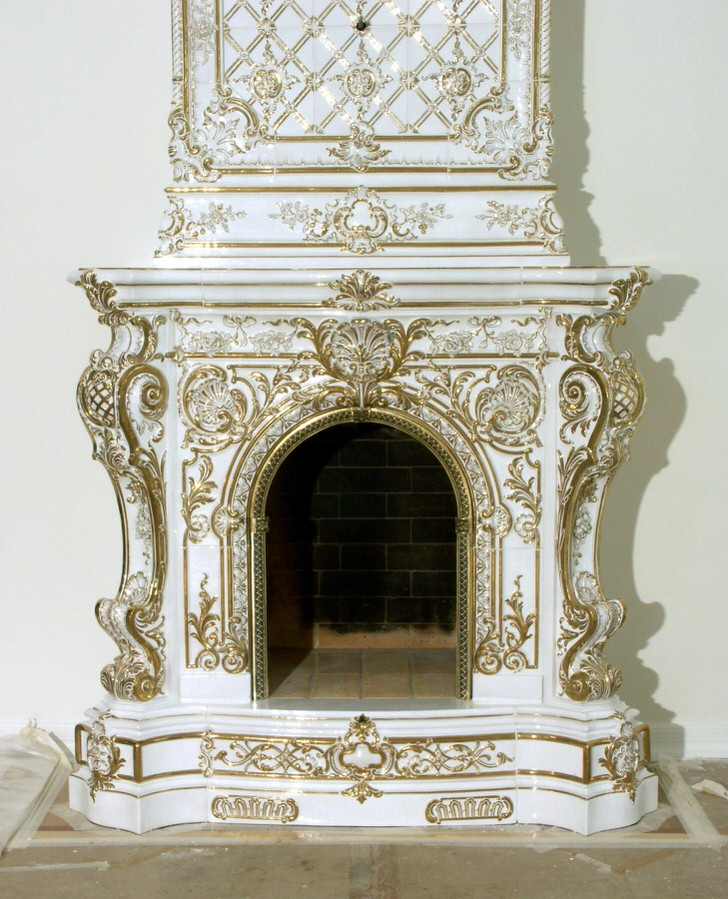 Роскошный изразцовый камин в стиле барокко украшен золотыми элементами декора.