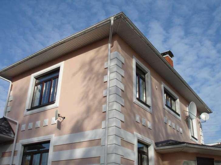 Нежно-персиковые стены дома украшает классическая фасадная лепнина.