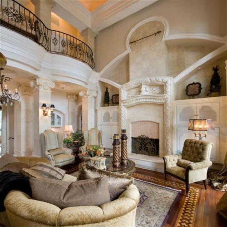 Помпезная гостиная в стиле ампир с декорированным белой лепниной камином. Внимание притягивают белые колонны украшенные небольшими светильниками.