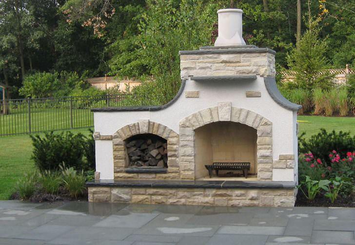 Элегантный уличный камин для загородного дома. Практичный камин имеет отсек для хранения дров, которые можно использовать для топки.