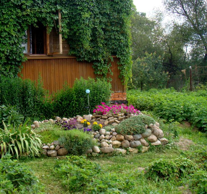 Клумба из многолетников в саду загородного дома.