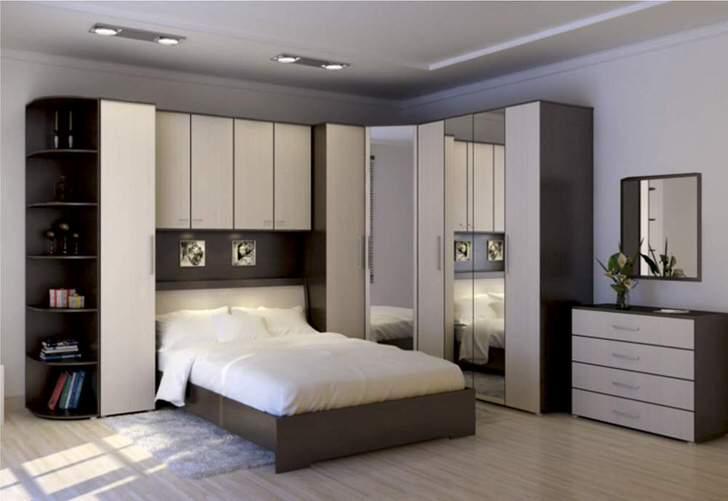 Функциональная угловая стенка для спальни. Правильно спроектированное пространство остается просторным и не загроможденным. Место сэкономить позволяют навесные шкафчики над кроватью.