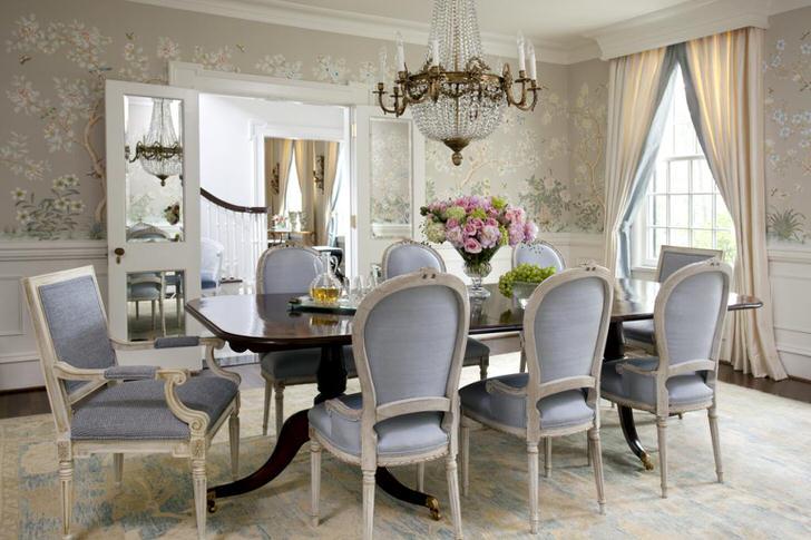 Столовая в стиле неоклассика оформлена в бледно-голубом и светло-сером цветах. Цветочные обои нежно смотрятся в сочетании с белыми высокими плинтусами.