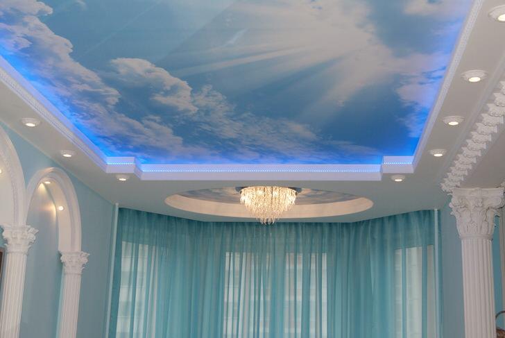 Просторная гостиная в стиле барокко оформлена при помощи натяжных потолков с фотопечатью.