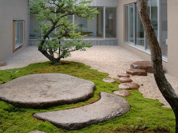 """Сад примечателен сочетанием участков зелени с """"голыми"""" поверхностями из камня. Стиль модерн с изысканной тропинкой из крупных каменных глыб."""
