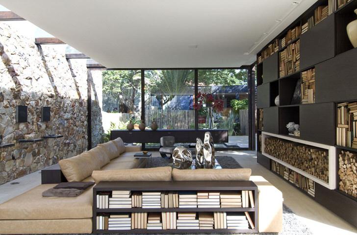 Гостевая комната в большом доме на юге Италии. Панорамные окна пропускают в гостиную достаточное количество света. В соответствии стилю лофт стена отделана природным камнем.