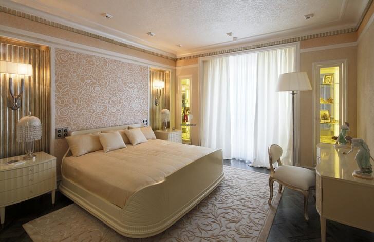 Спальня в светло-бежевых тонах с широкой кроватью отлично подойдет для отдыха и сна. Дизайнерский проект составлен грамотно. В соответствии со стилем арт-деко подобрано эксклюзивное освещение.