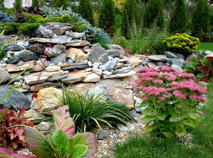 Интересным вариантом становится использование природного камня в качестве ограждения для клумбы.