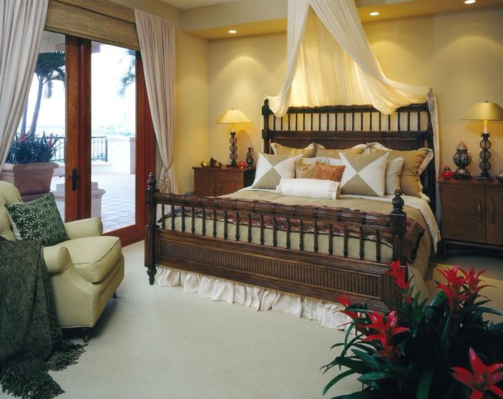 Роскошная кровать в спальне в стиле эклектика. Балдахин над кроватью, легкие шторы на дверях, ведущих на веранду, делают помещение уютным и романтичным.