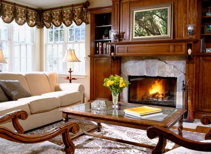 Отделка камина из природного камня гармонично смотрится со стенкой из дерева для гостиной, поскольку стиль кантри примечателен использованием в оформлении именно натуральных материалов.
