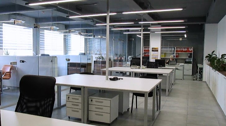 Просторный офис оформлен в лофт стиле. Белая корпусная мебель гармонично вписывается в общий интерьер помещения.