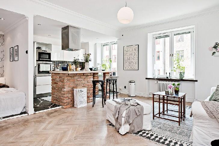 Квартира студия оформлена в скандинавском стиле. Кухня отделена от гостиной барной стойкой из кирпича.