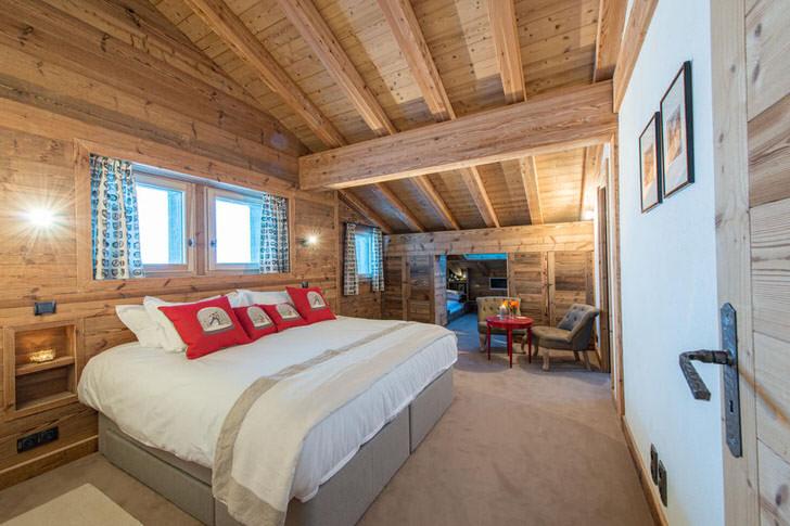 Просторная спальня на втором этаже загородного дома из деревянного сруба. В соответствии со стилем кантри искусственный свет в комнате приглушен.