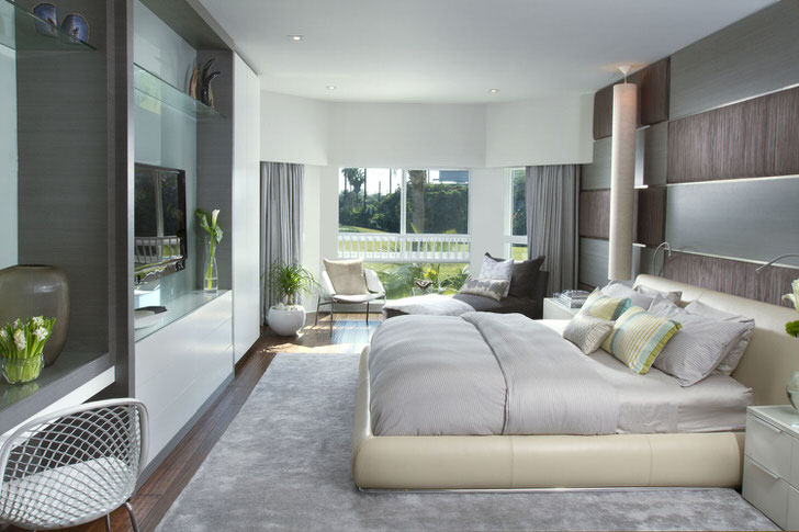 Мягкая, объемная кровать в спальне в модерн стиле. Мебель с глянцевой поверхностью выгодно вписывается в общую композицию интерьера.