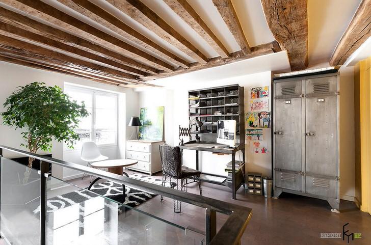 Деревянные балки под потолком, большое количество света, специфическая мебель свидетельствуют об использовании дизайнером принципов стиля лофт.