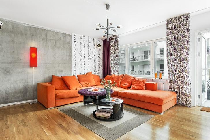 Скандинавскому стилю присуще использование теплых оттенков в оформлении интерьера. Мягкий диван оранжевого цвета органично смотрится на фоне стен холодно-серого оттенка.