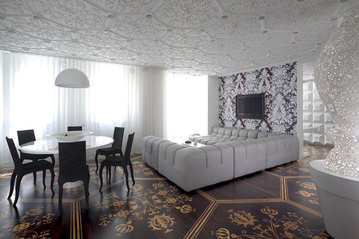 Контраст белого и темно-коричневого цвета в гостиной в модерн стиле. Огромный диван П-образной формы для длительных просмотров фильмов и любимых передач.
