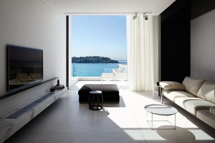 Чудесная светлая гостиная с видом на море. Стиль хай тек предлагает максимально использовать в освещении естественный свет.