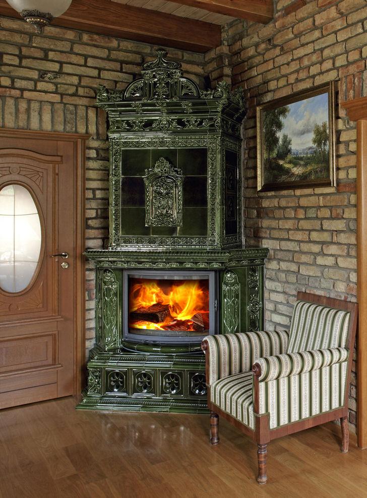 Изразцовый камин органично смотрится на фоне кирпичной кладки. Вычурный дизайн дополняет правильно подобранная мебель.