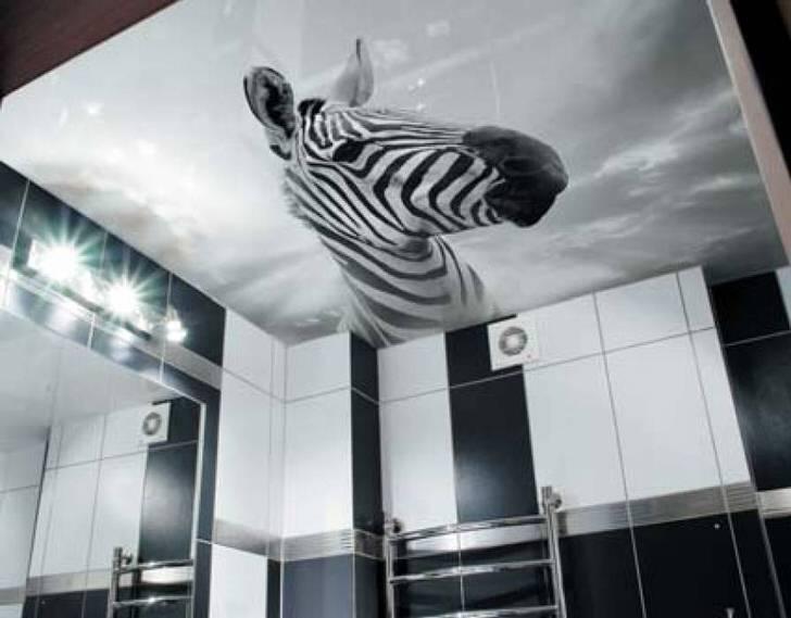 Необычное решение для оформления черно-белой ванной комнаты - изображение зебры на натяжных потолках с фотопечатью.