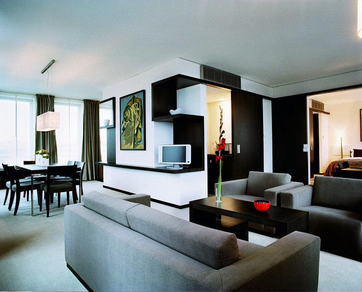 Зоны отдыха и столовая часть гостиной освещаются низко свисающими светильниками простых геометрических форм.