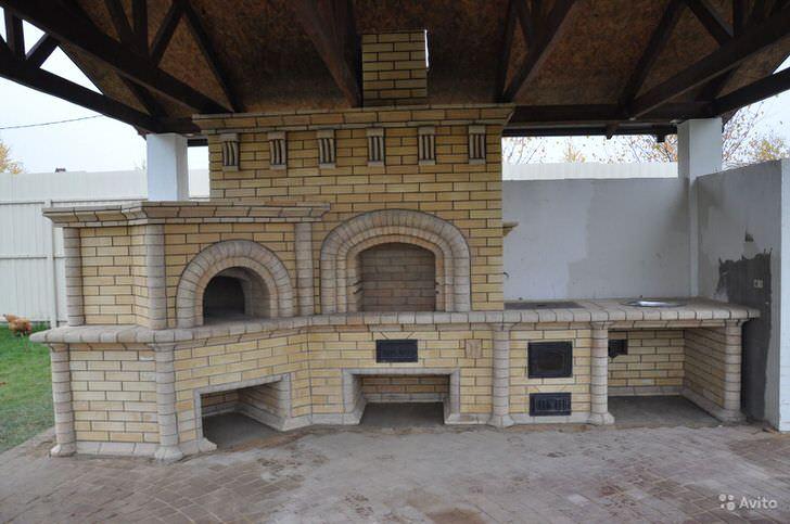 Крупный уличный камин во дворе дома под навесом - отличное решение для людей, которые стремятся больше времени проводить на свежем воздухе.