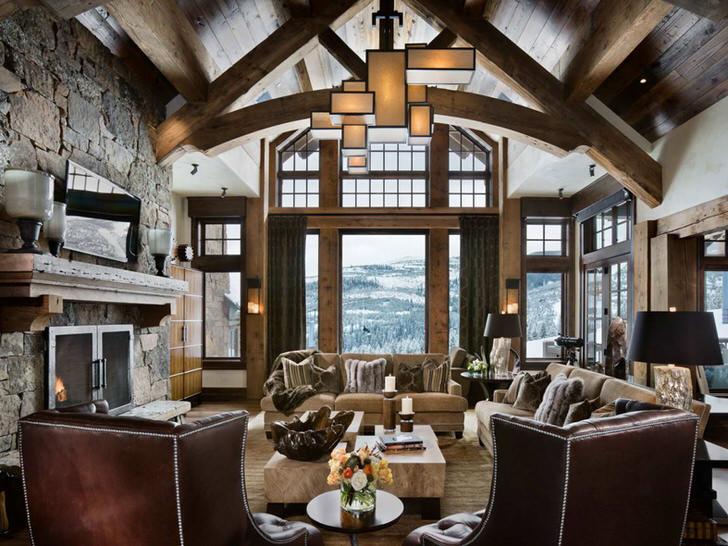 Уютная гостиная в кантри стиле с панорамными окнами. В соответствии современному стилю для интерьера верно подобрано освещение.