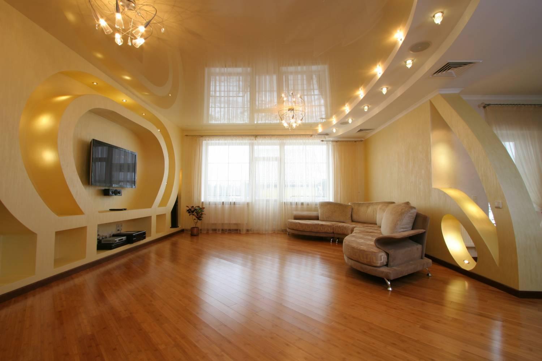 Нежно-персиковый потолок в цвет общей отделке помещения оснащен освещением, поделенным на зоны. Светодиодные светильники над диваном и две люстры по разные стороны комнаты.