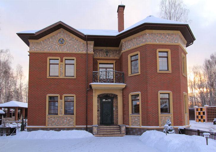 Необычная архитектура загородного дома из кирпича дополнена декором из лепнины. Оконные и дверные проемы из керамической лепнины гармонично вписываются в общую стилистику экстерьера.