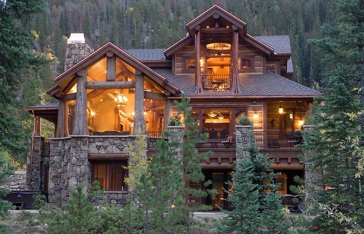 Дизайн дома в стиле рустик выгодно сочетает элементы фасада из массивного сруба дерева и панорамное остекление.