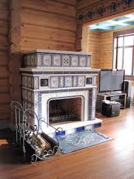 Стильный изразцовый камин шикарно вписывается в интерьер деревянного, охотничьего домика.
