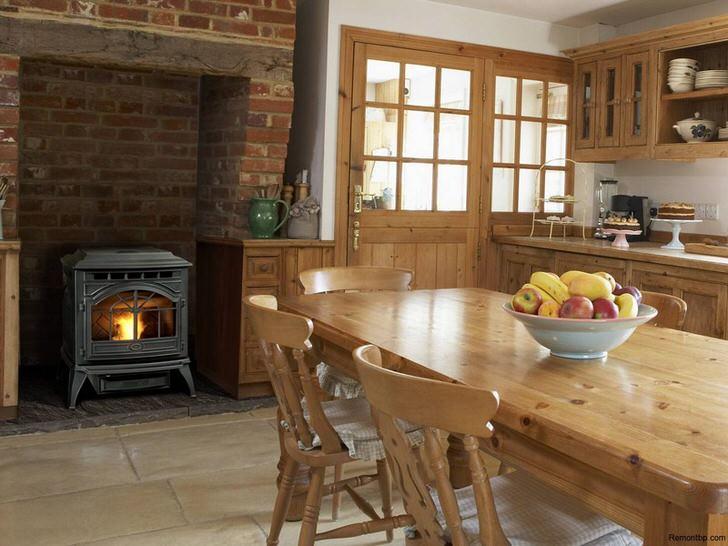Каминная топка с нише из камина идеально вписывается в общий интерьер кухни в стиле кантри.
