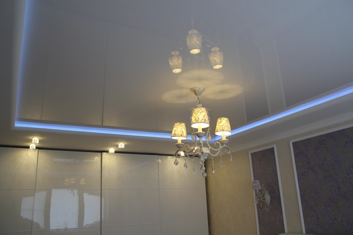 Неоновая полоса, разделяющая ярусы натяжного потолка, - необычное и эффектное освещение для комнаты.