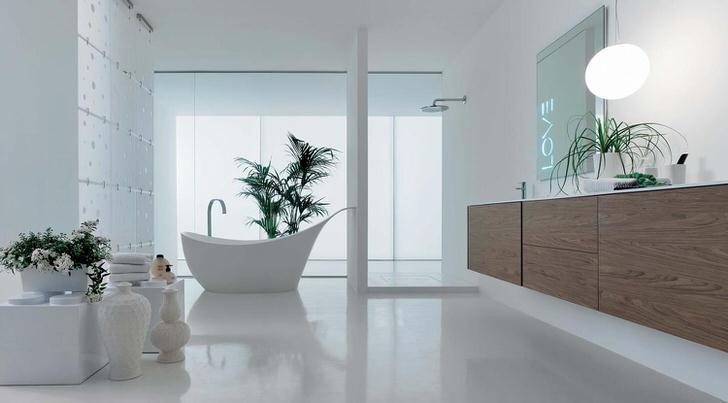 Большая ванная в стиле хай-тек выполнена в светлых тонах. Освежают интерьер комнаты живые цветы.