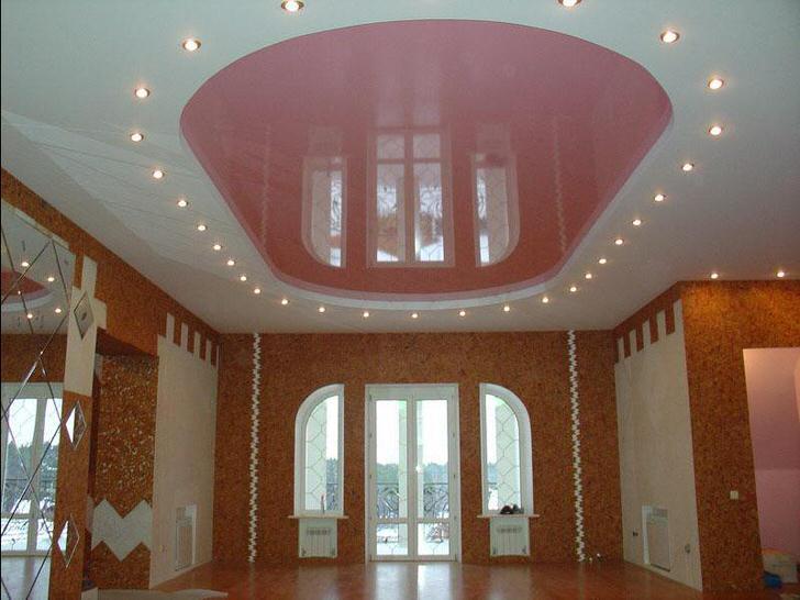 Розовый овал натяжного потолка со светодиодным освещением в большой комнате в загородном доме.