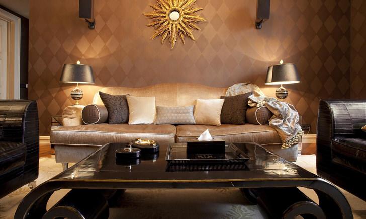 Роскошная гостиная в стиле арт деко с правильно подобранным освещением. Стильная обстановка украшена своеобразной декоративной деталью, напоминающей солнце.