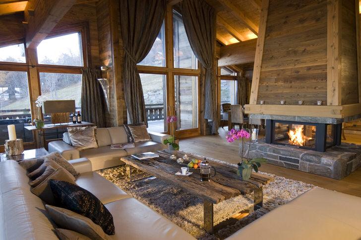 Просторная гостевая комната в стиле шале способствует сближению человека и природы. В соответствии с требованиями стиля большие окна в деревянных рамах пропускают в комнату достаточное количество дневного света.